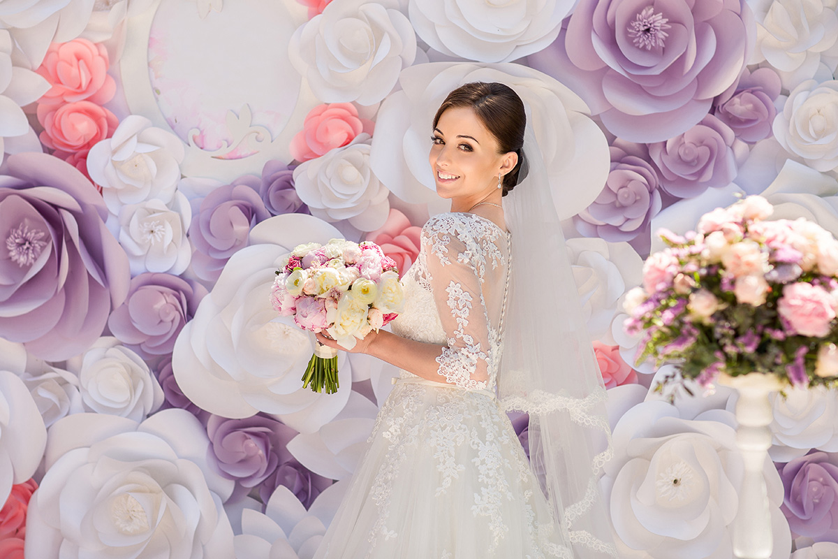 Bride In Front Of A Wall Of Paper Flowers